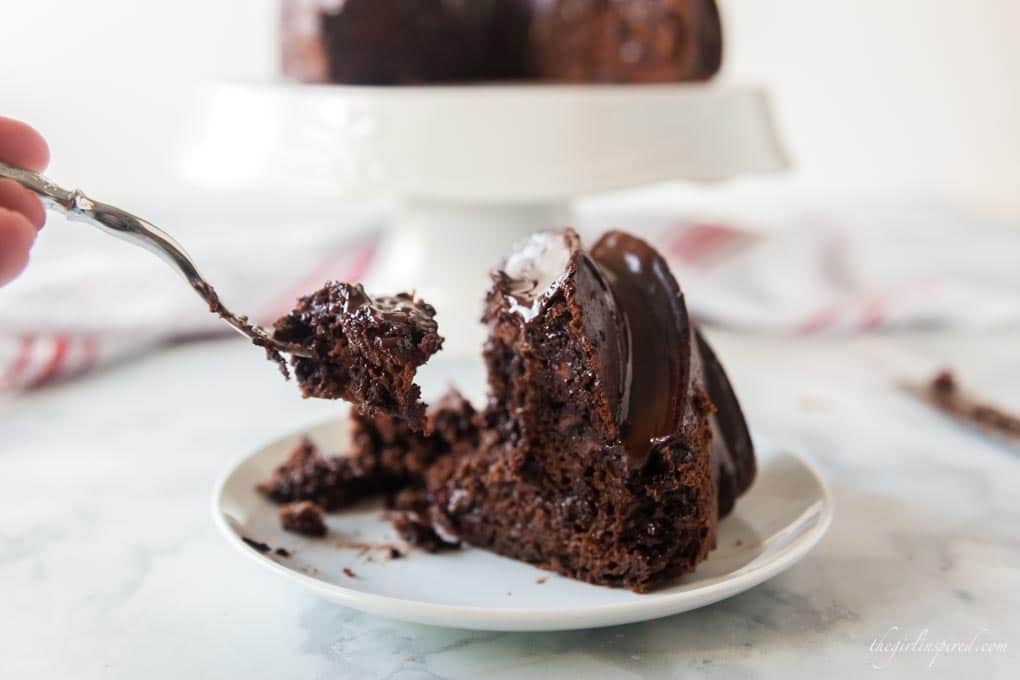 forkful of chocolate cake from cake slice on white plate