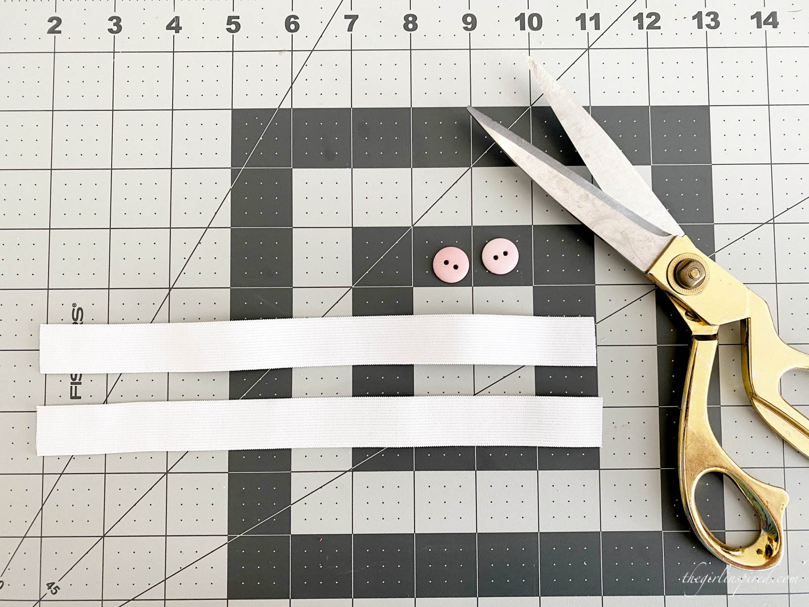 two strips of elastic, pink buttons, and gold-handled scissors on grey grid cutting mat