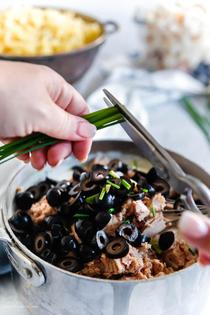 scissors being used to cut chives into saucepan with tuna and olives