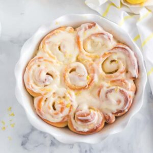 baked sweet rolls in white pie plate, with white dishes, lemons, and dish towel in background