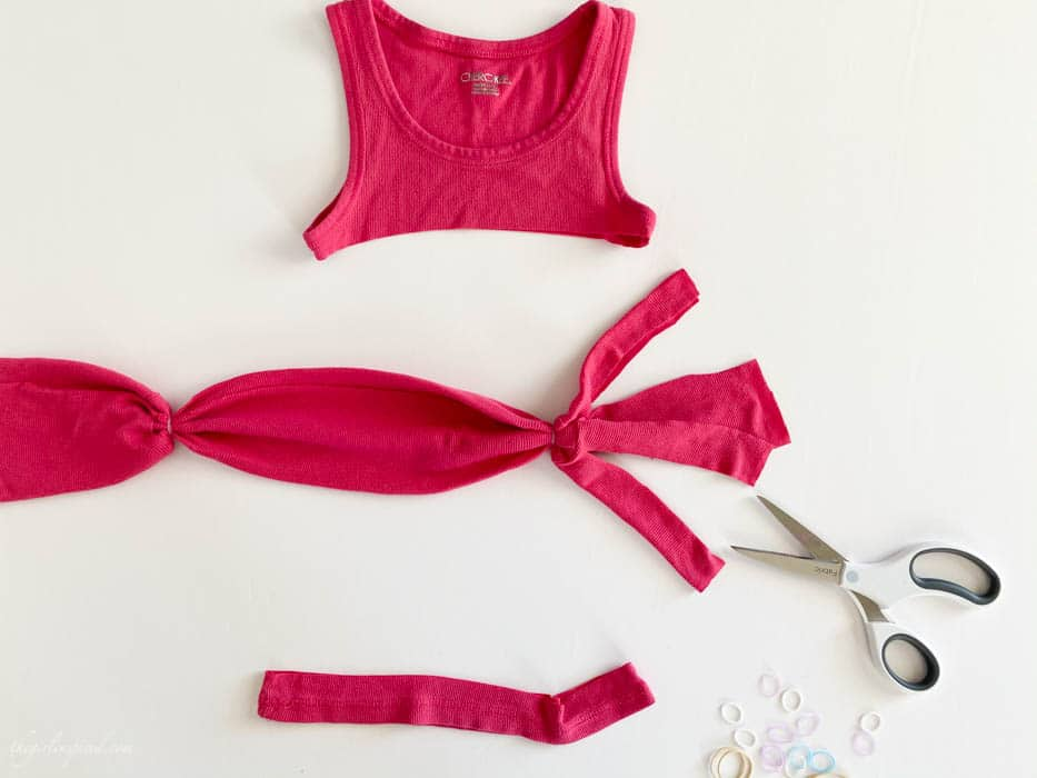 white scissors, elastic bands, and pieces of pink tank top