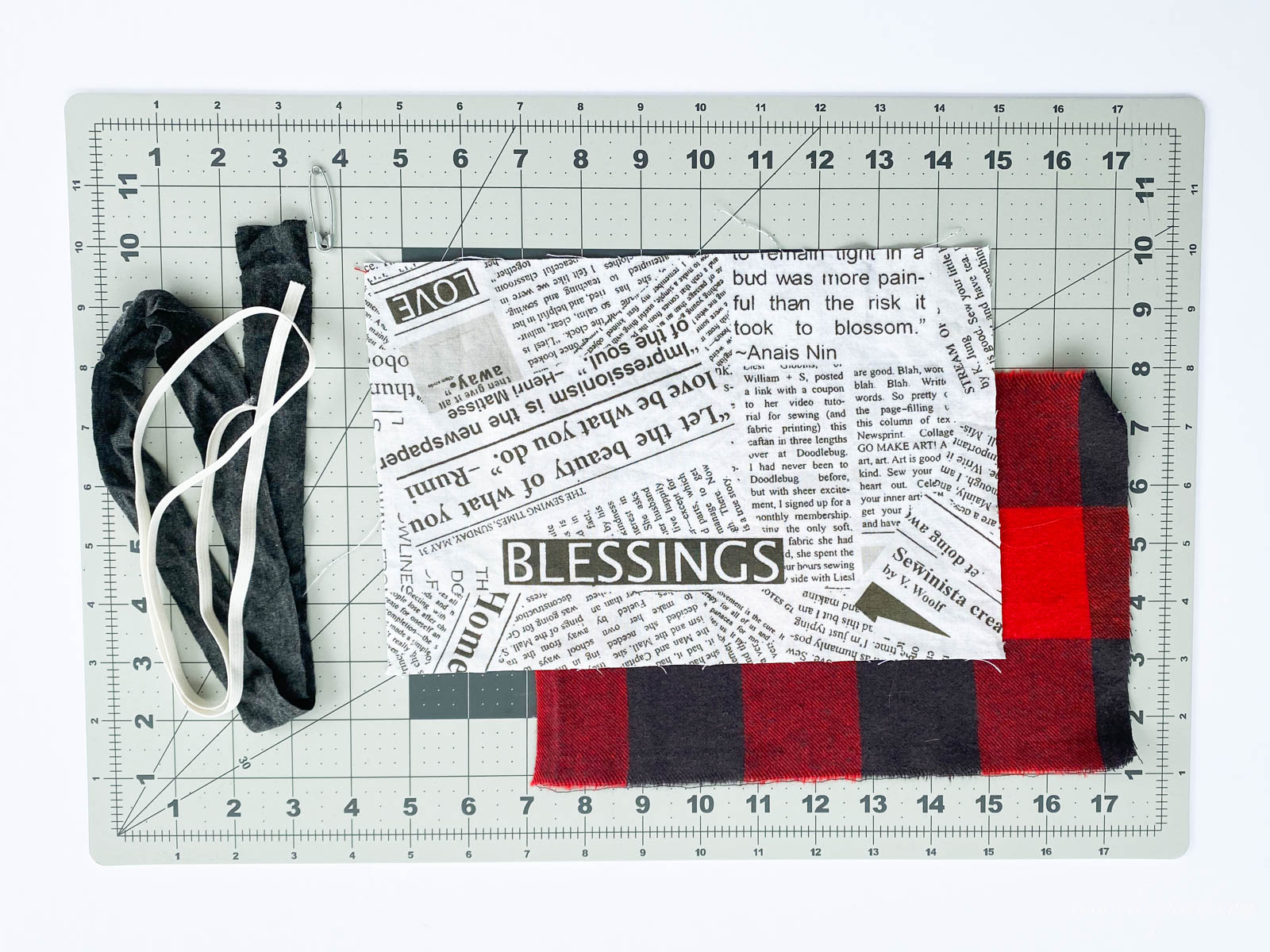 newsprint patterned fabric, red and black checked fabric, elastic, on a rulered mat