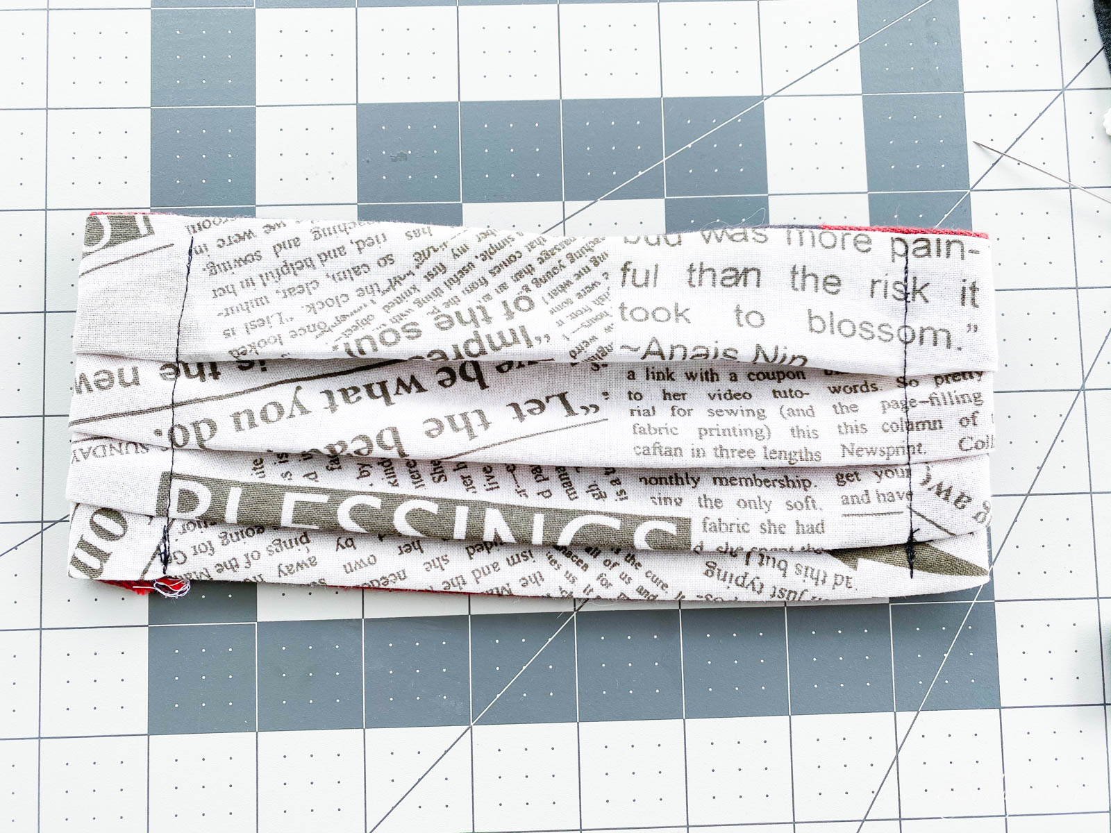 front side of newsprint serger fabric mask on rulered mat