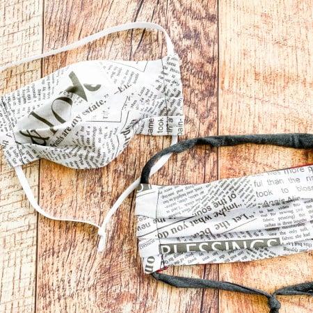 finished serged newsprint fabric mask on wood plank background
