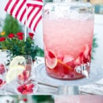 photo collage with text overlay showing strawberry sangria in large glass drink dispenser on pedestal stand, lemon wedges and fresh berries in wine glasses on table and American flag in the background and closeup of glass of sangria