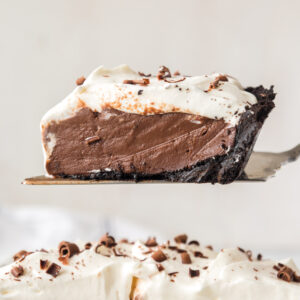slice of chocolate cream pie on serving spatula above pie in white pie plate