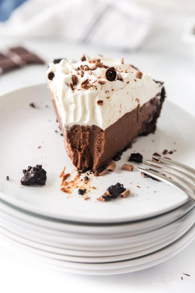 slice of chocolate cream pie on stack of white plates with one bite removed