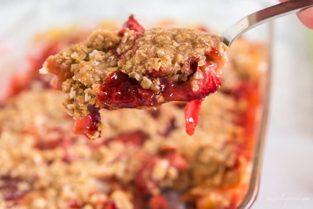 Closeup of spoonful of strawberries and oat crisp topping