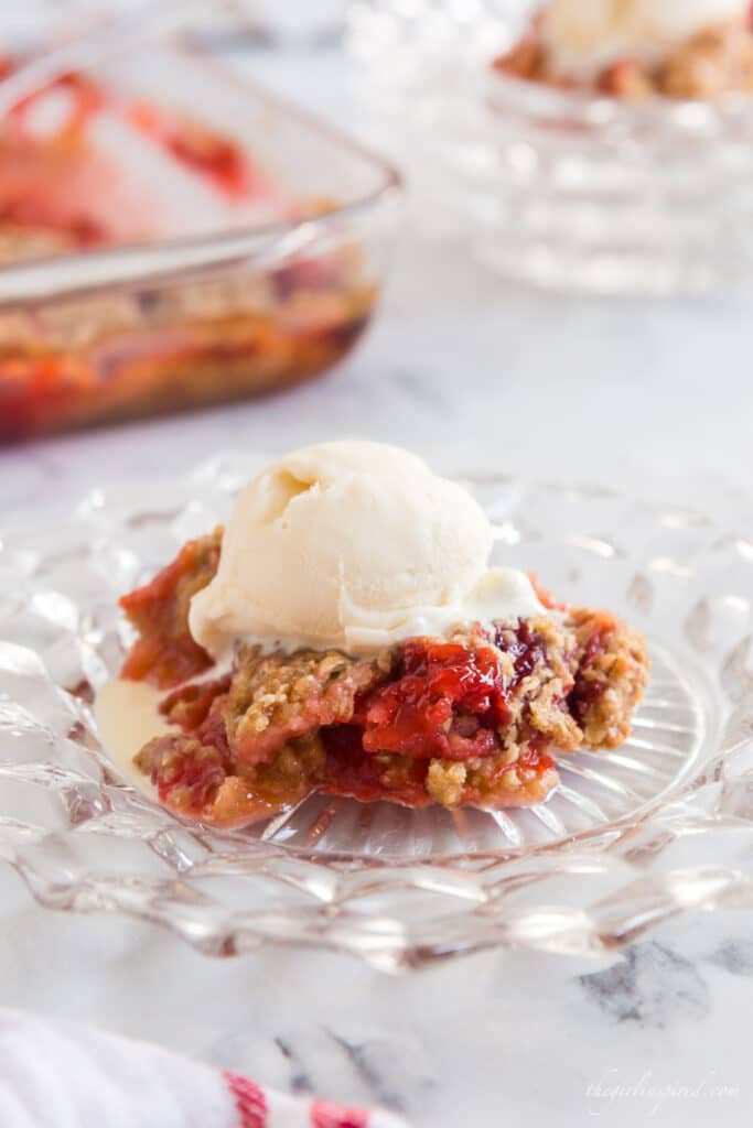Serving of strawberry rhubarb crisp with a scoop of vanilla ice cream on top on glass serving dish