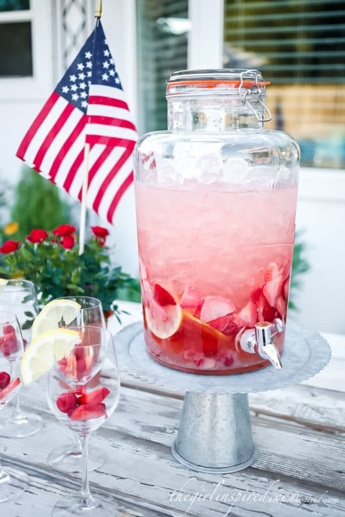 strawberry sangria in large glass drink dispenser on pedestal stand, lemon wedges and fresh berries in wine glasses on table and American flag in the background