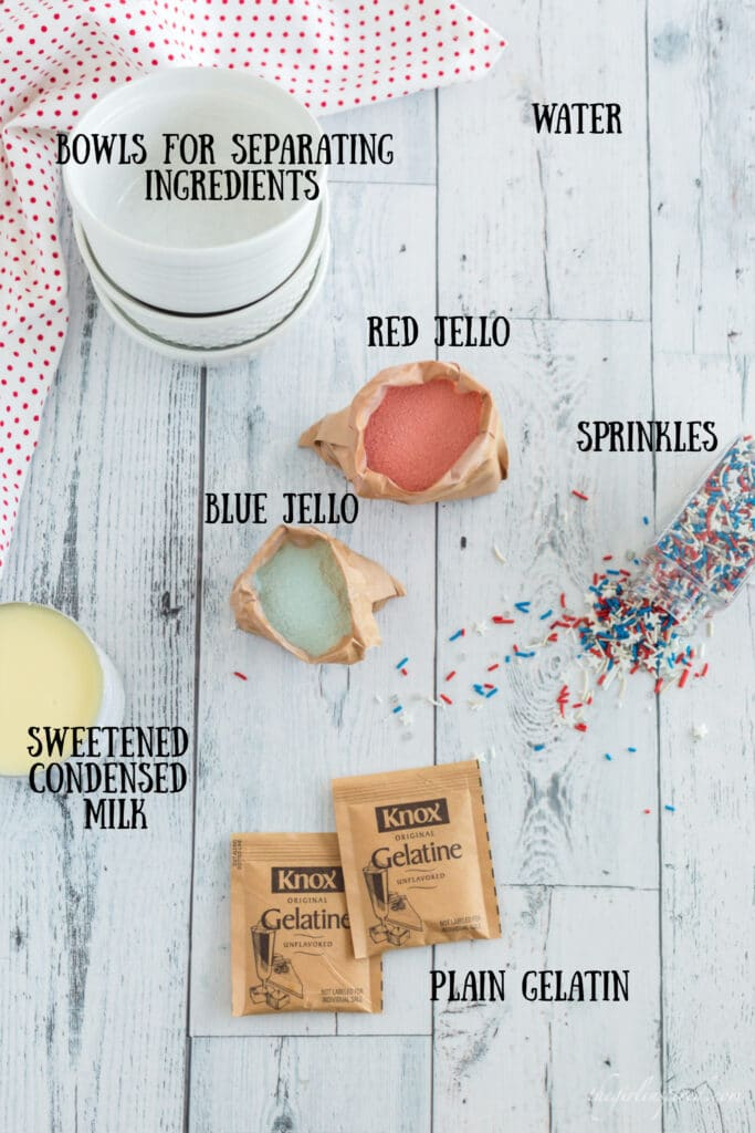overhead photo of jello cup ingredients: white bowls, paper packets of red and blue jello, gelatin packets, can of sweetened condensed milk, and red white and blue sprinkles