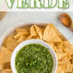 salsa verde in white chip'n'dip serving bowl with tortilla chips, wooden spoon, cilantro and jalapeño slices and wooden cutting board with text overlay