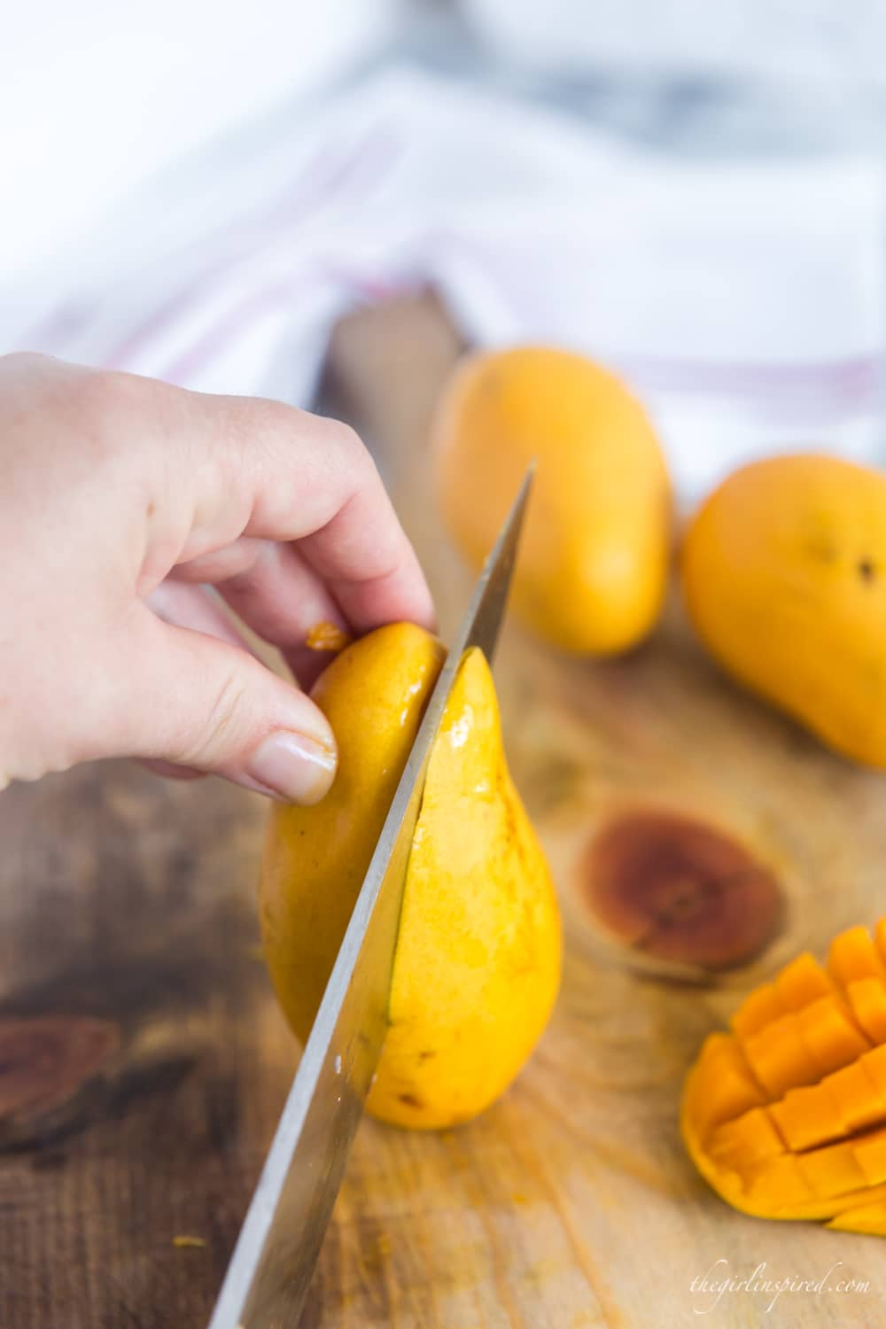 knife cutting a mango on wooden cutting board with mangos in the background