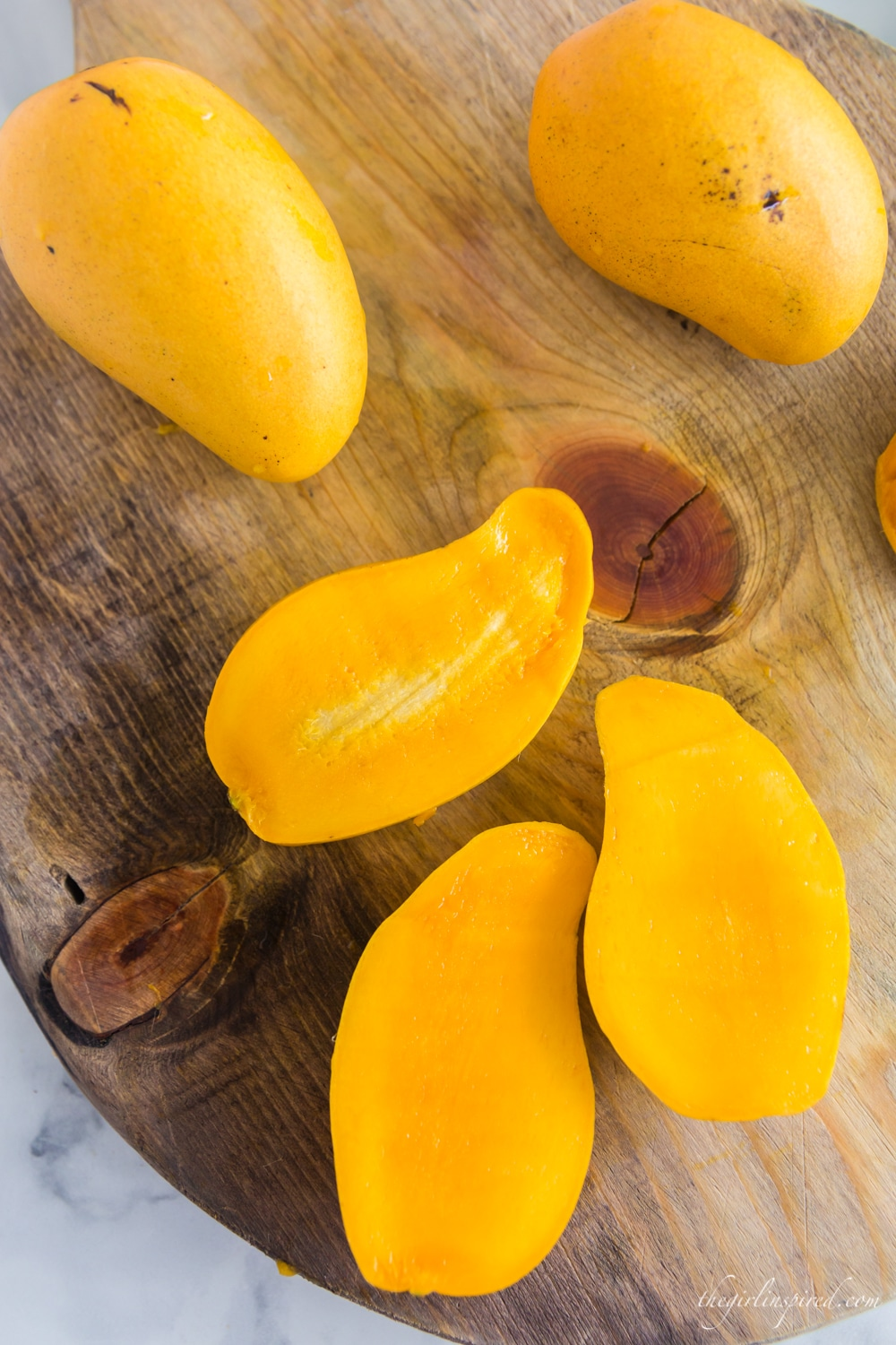 two open halves of a mango, mango seed, and two whole mangos on wooden cutting board