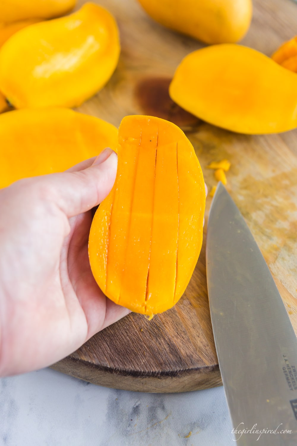 knife, cutting board and lengthwise slice pattern in mango half