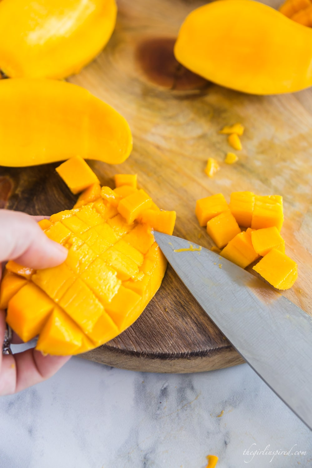 knife cutting chunks of mango off skin