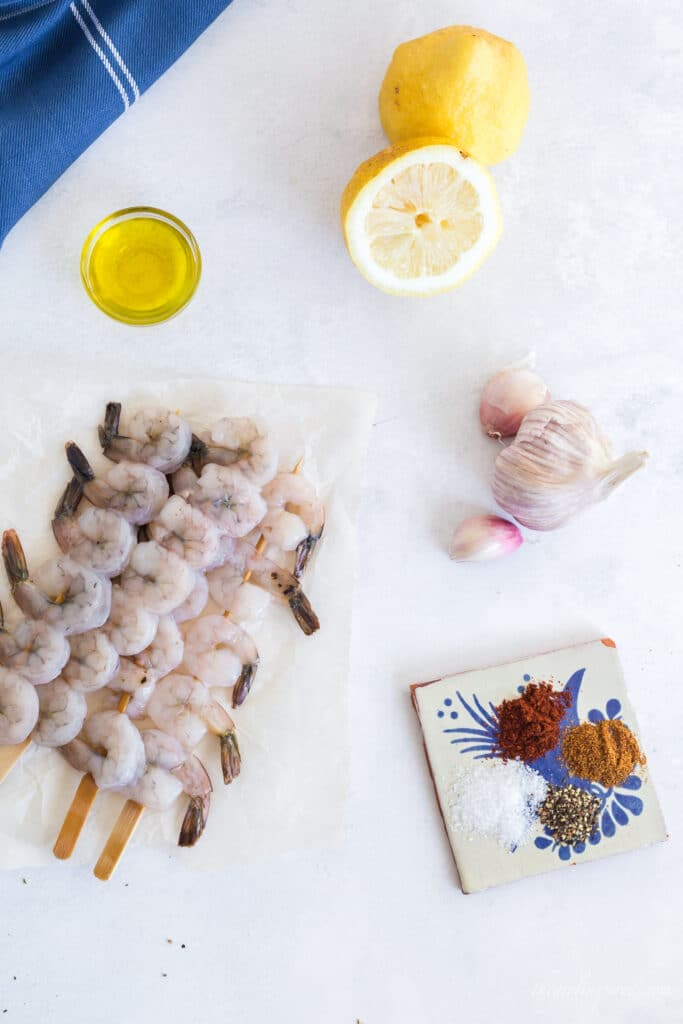 raw shrimp on skewers, bowl of olive oil, lemon, garlic head, spices on blue and white tile