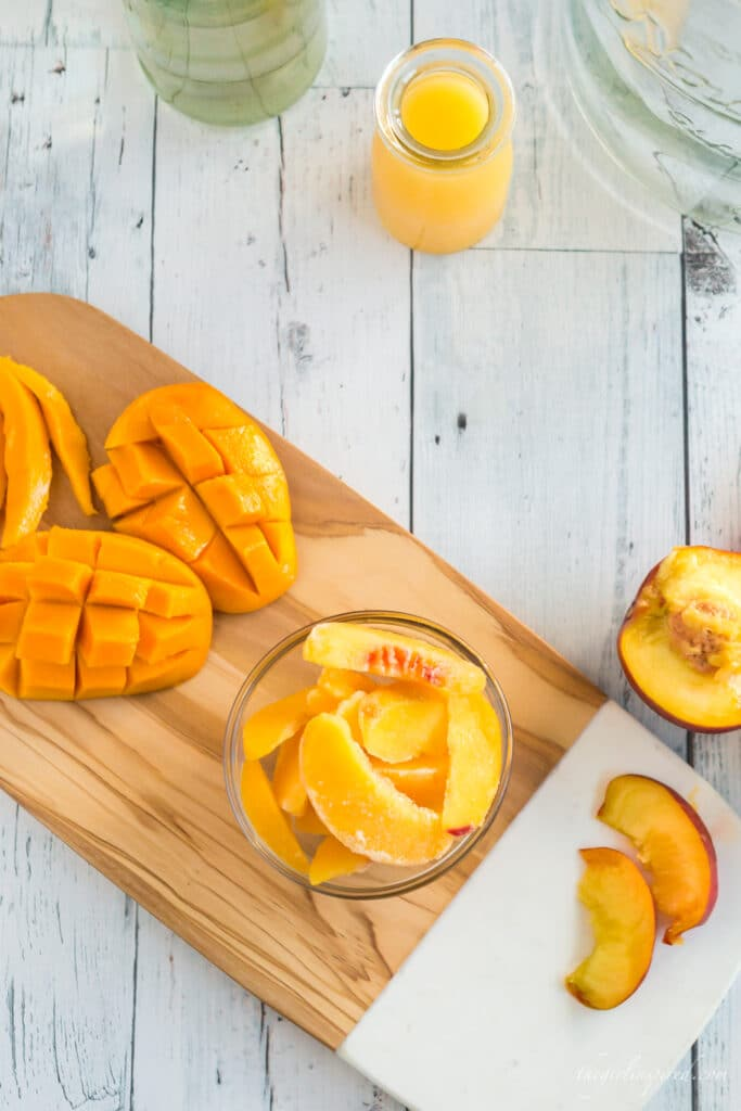 marble and wooden cutting board with sliced peaches and mango and a carafe of orange juice
