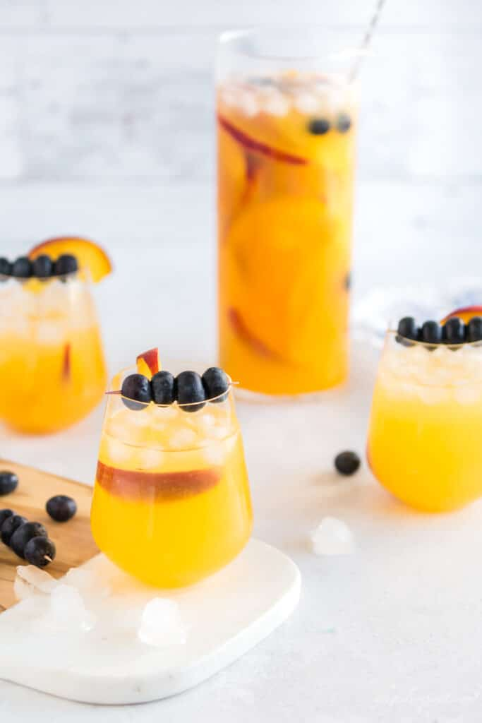peach sangria in a carafe and wine glasses with blueberries on a toothpick and a peach slice for garnish
