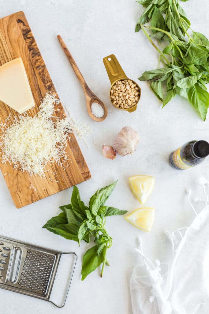 grated parmesan cheese on wooden board, salt in wooden spoon, toasted pine nuts in gold measuring cup, fresh basil, garlic cloves, lemon wedges, cheese grater, bottle of olive oil and a white linen