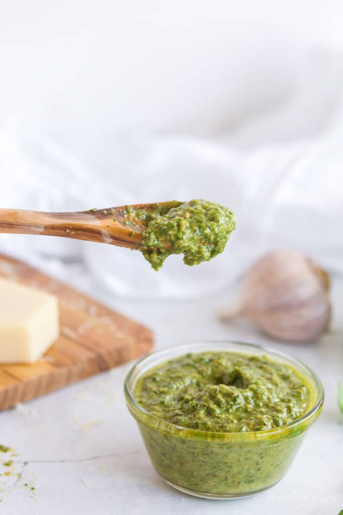 Wooden spoon scooping pesto from glass bowl, wooden cutting board with parmesan cheese, garlic cloves and white linen in background