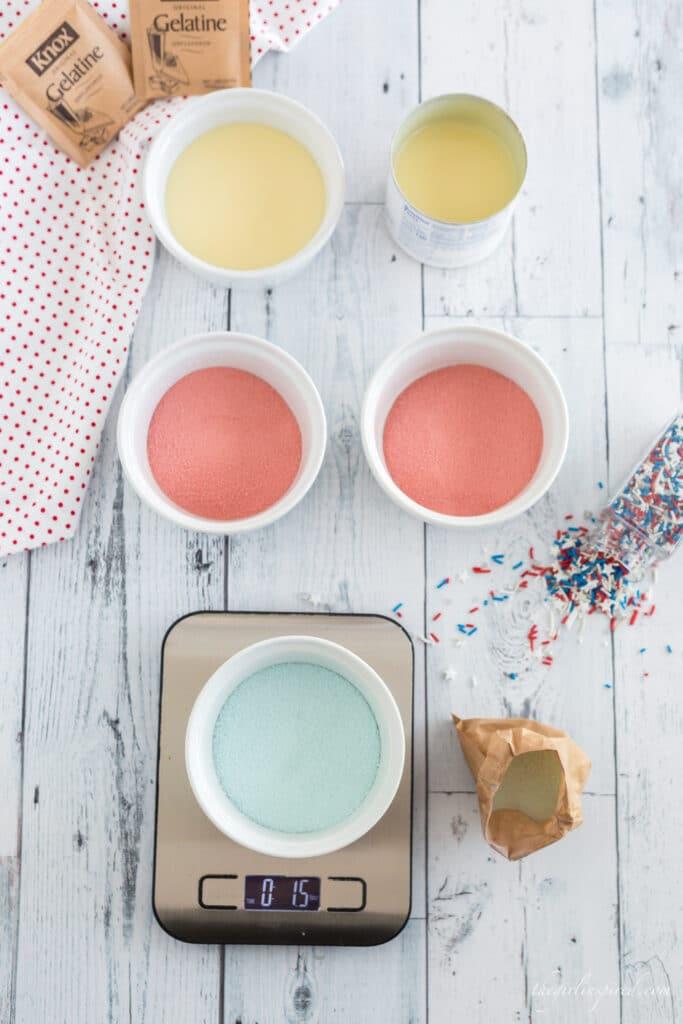 two white bowls of red jello powder, one white bowl of blue jello powder on a digital scale, red white and blue sprinkles, white bowl and can of sweetened condensed milk, white and red linen