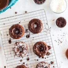 chocolate baked donuts on cooling rack with chocolate frosting dripping over the tops and coconut, chocolate chips, or sprinkles on top, aqua linen in background