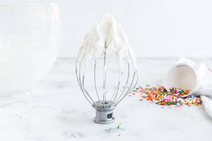 white frosting on a mixer whisk attachment standing next to glass bowl of frosting, tipped over bowl of sprinkles in the background