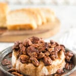 browned pecans and brown sugar over brie in a baking dish on a wooden serving board with slices of bread in the background