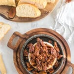 browned pecans and brown sugar over brie in a baking dish on a wooden serving board with sliced bread in background