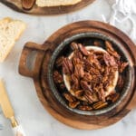 browned pecans and brown sugar over brie in a baking dish on a wooden serving board