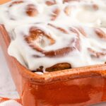 side view of orange baking dish with baked and frosted pumpkin cinnamon rolls and text overlay