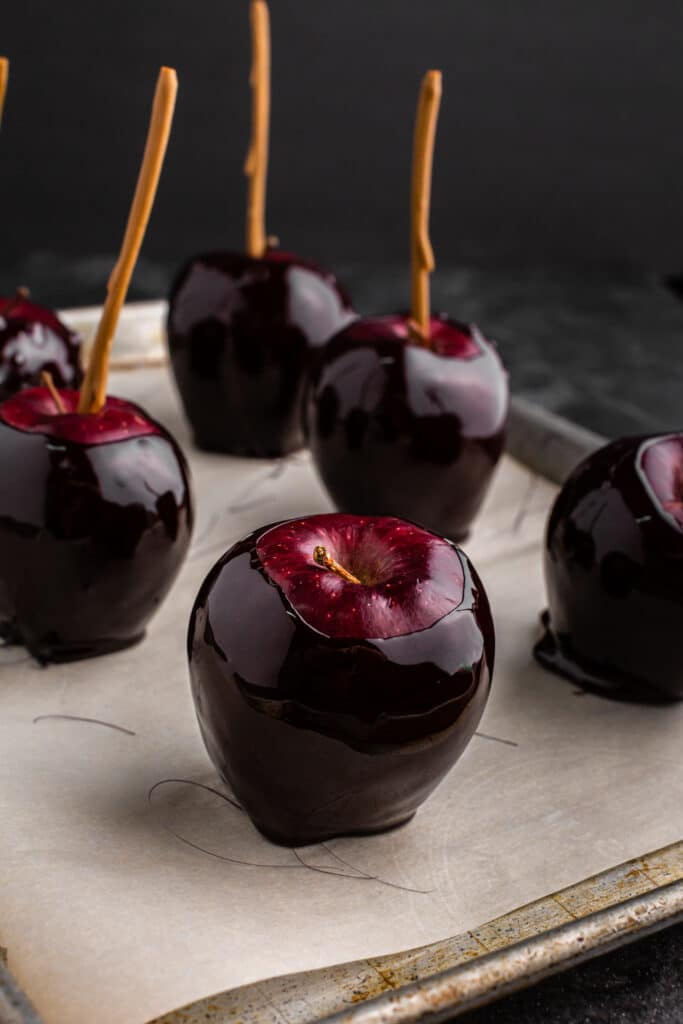black candy apples on parchment paper on baking sheet