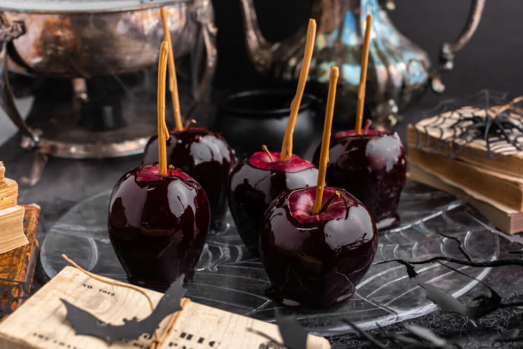 black candy apples on plate with black background and misty bowl and pitcher in background