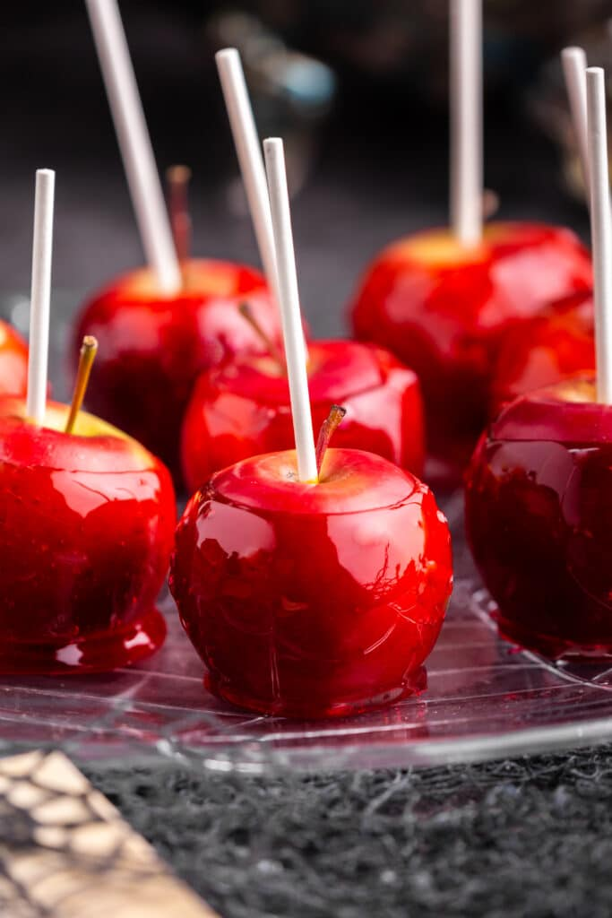 close up of red candy apples on a plate on black backdrop