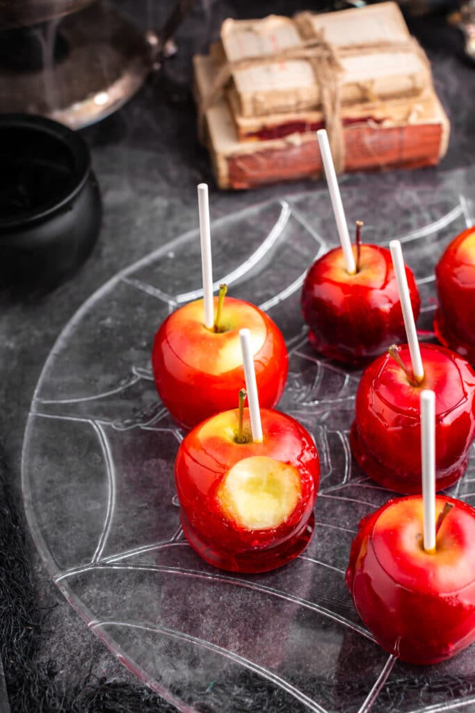 red candy apples on plate with stack of books in background and bite taken from one of the apples