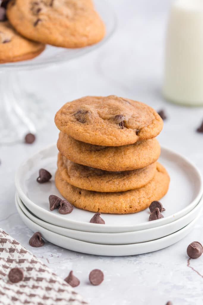 stack of pumpkin chocolate chip cookies on white plates with linen and glass of milk in background