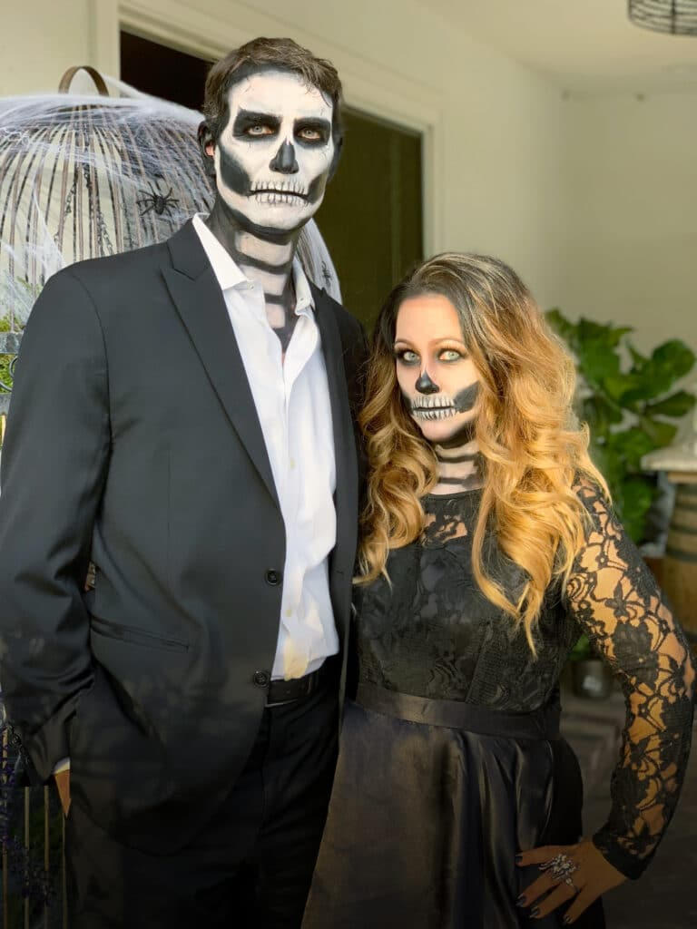 man and woman dressed in black suit and black lace dress with skeleton face makeup