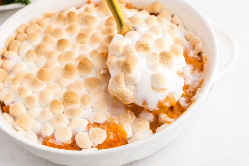 closeup of gold spoon scooping candied yams with toasted marshmallows from white dish