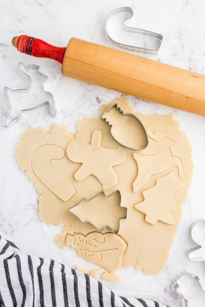 cookie dough rolled out, cookie cutters, some shapes cut out with rolling pin and dishcloth