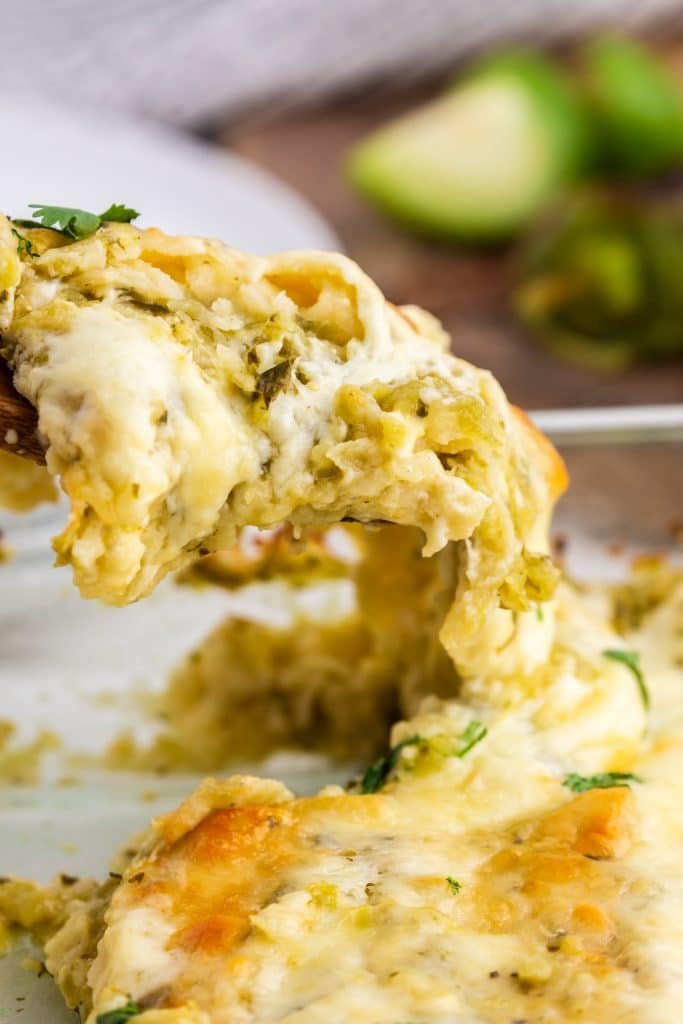 close up photo of green sauce cheese enchilada scoop