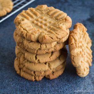 stack of peanut butter cookies with one cookie tilted against the side of stack; cooling rack with cookies in background