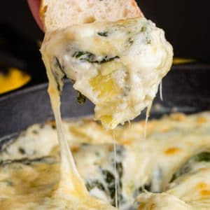 crostini scooping melted cheesy spinach artichoke dip