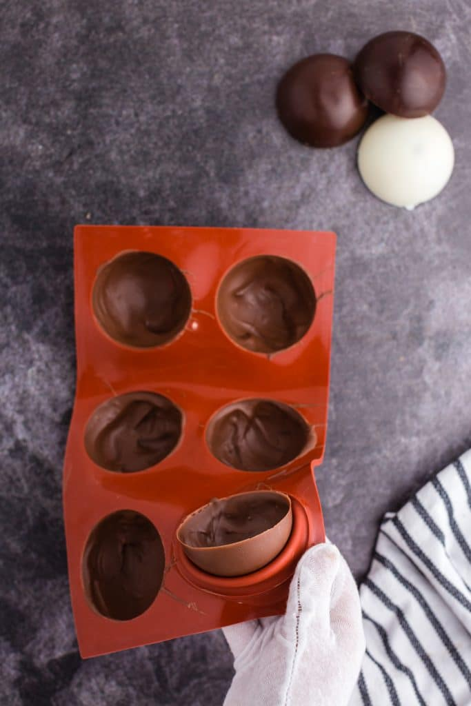 gloved hand pressing molded chocolate out of mold