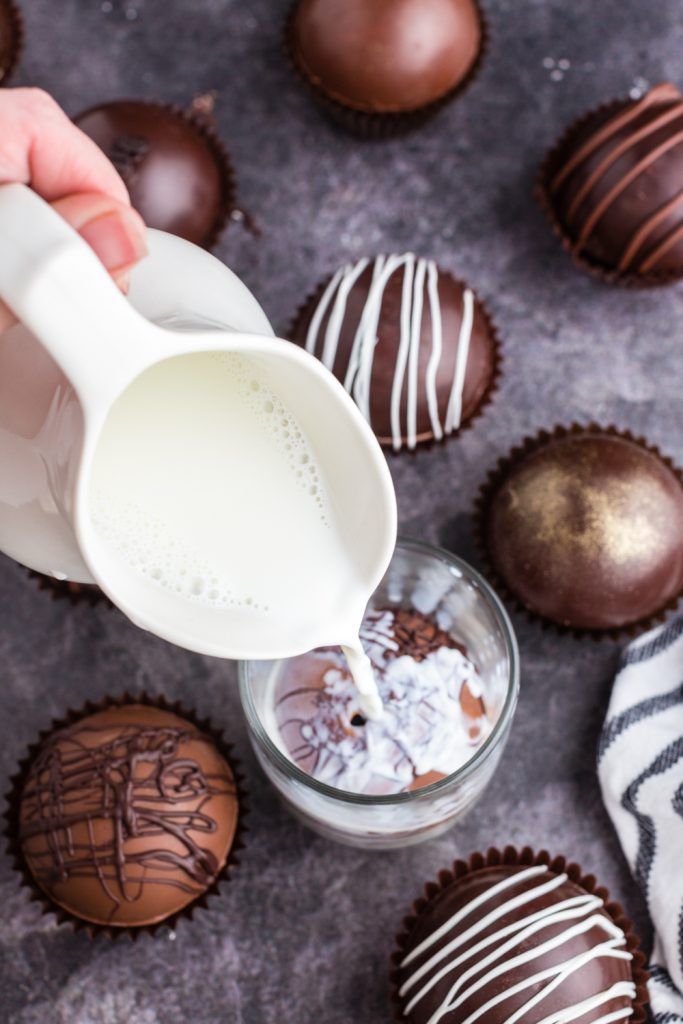 white pitcher pouring milk over melting hot chocolate bomb in glass mug