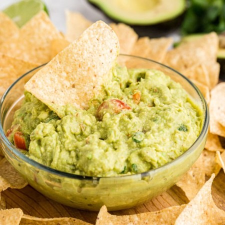 guacamole in clear glass bowl with chip dipping into it and chips around