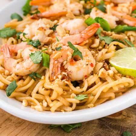big shrimp, cilantro, and green onions adorn this shrimp pad thai on white plate set on cutting board