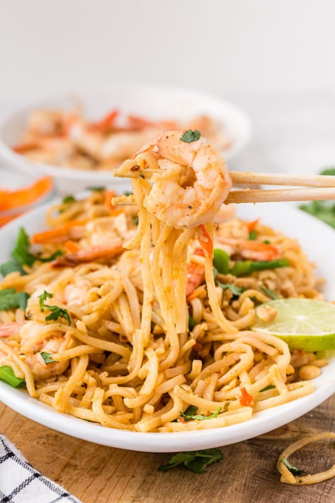 chopsticks lifting scoop of shrimp pad thai with big shrimp on top; pad thai on white serving platter