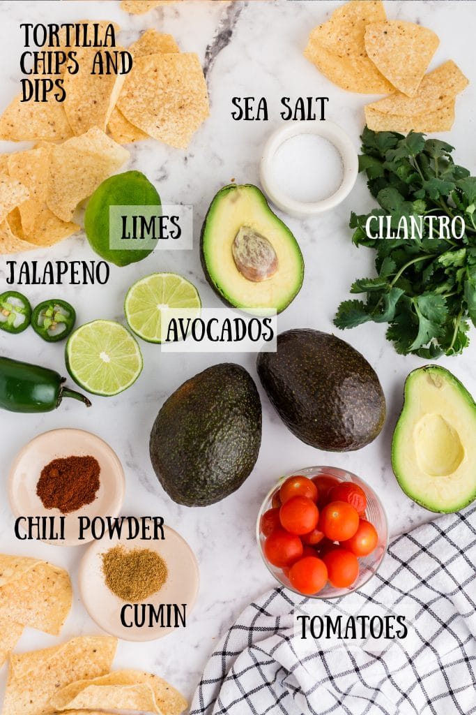 overhead photo of ingredients for the guacamole: avocados, tortilla chips, salt, limes, jalapeno, chili powder and cumin on little dishes, tomatoes in a glass bowl, cilantro