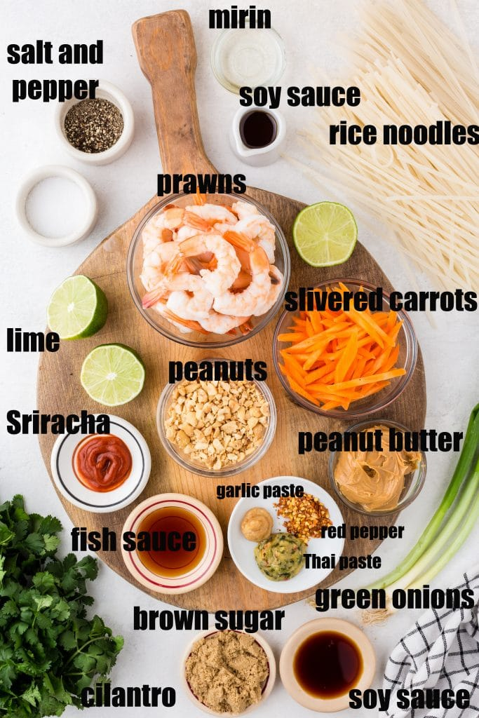 shrimp pad thai ingredients laid out in bowls and on cutting board
